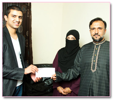 Adeem Younis presents Mohammad and Anila with Umrah Tickets.