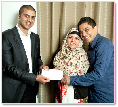 Adeem Younis presents Nanu and Rumana with Umrah tickets.